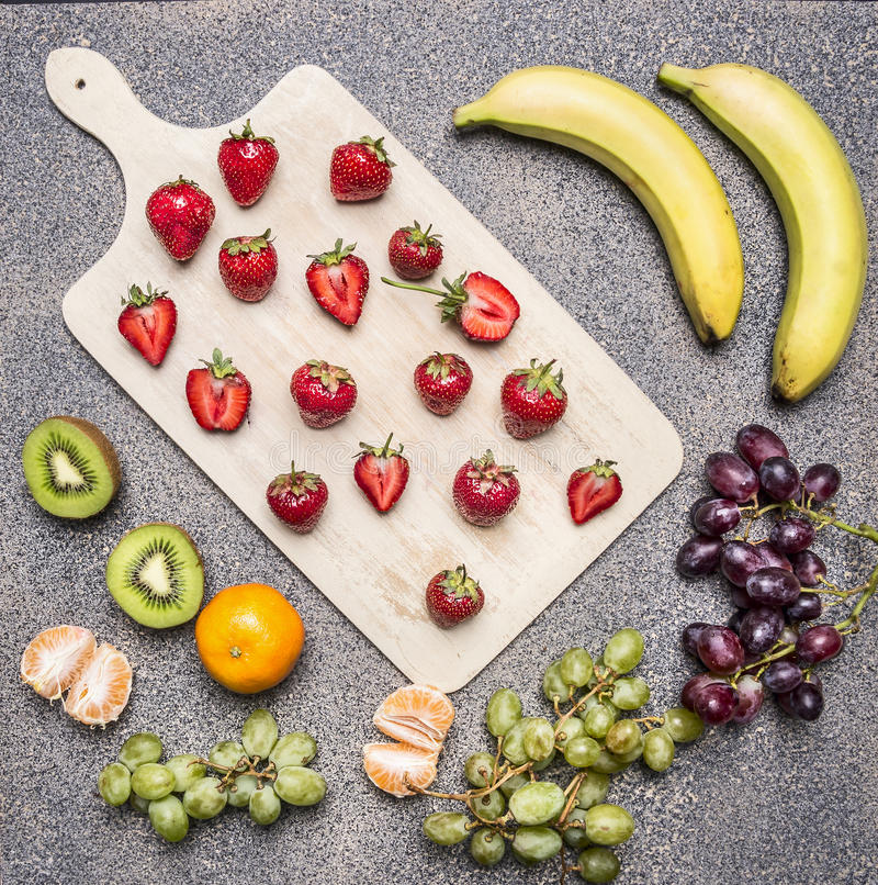Superfoods and healthy lifestyle or detox diet food concept bananas, strawberries, light dark grapes, kiwi and tangerine on a royalty free stock image