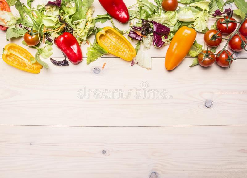 Superfoods and healthy lifestyle or detox diet food concept various vegetables and herbs on a white wooden table, cherry tomatoes,. Bell peppers, arugula, space stock images