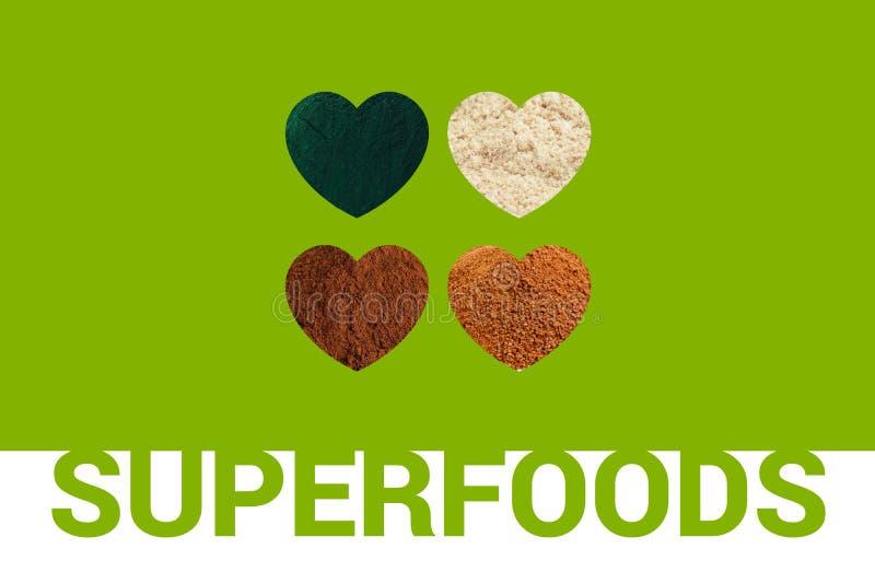 Superfoods tekst i cztery serca z spirulina proszkiem, cacao proszkiem, migdałową mąką i kokosowej palmy cukierem na zielonych pó obraz stock
