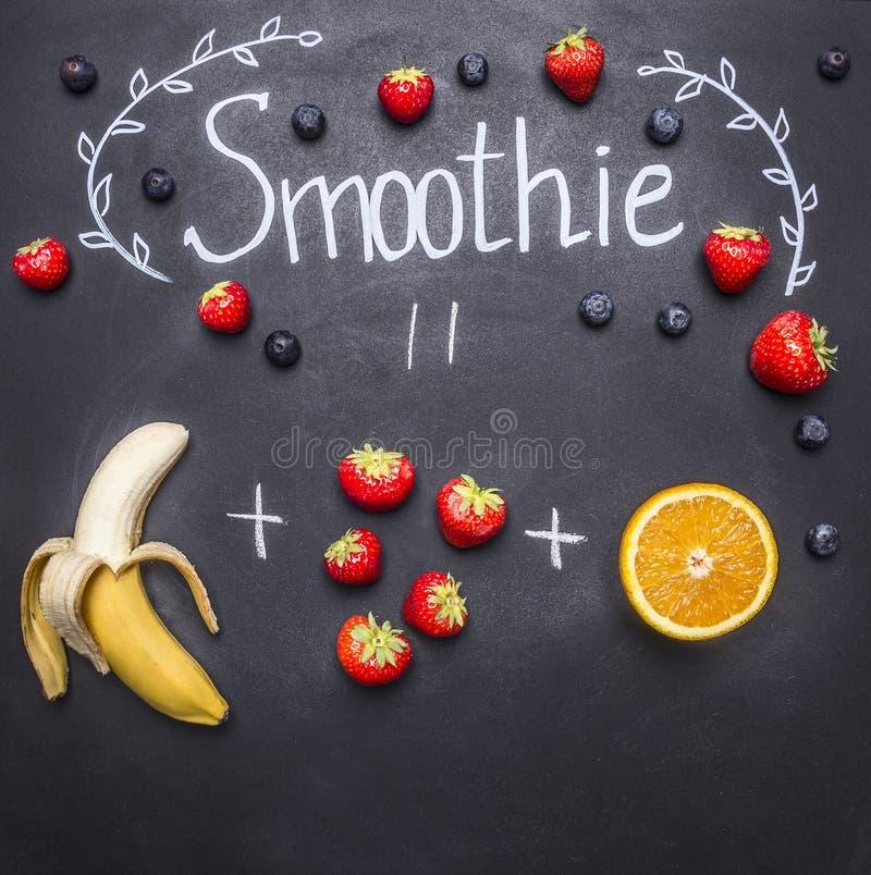 Superfoods y salud o concepto de la comida de la dieta del detox que cocina el smoothie con los plátanos y las fresas, el tablero imágenes de archivo libres de regalías