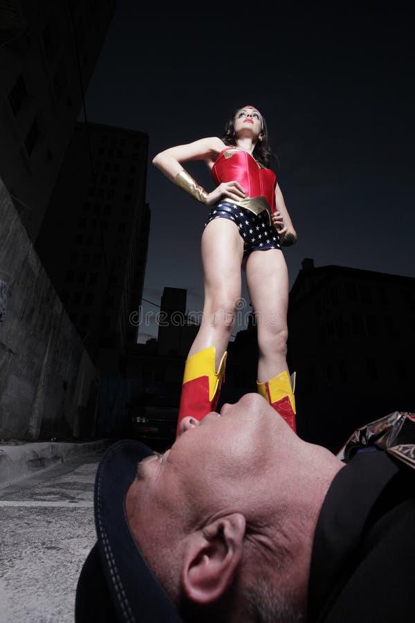 Superheld, der über dem schlechten Schuft steht lizenzfreies stockfoto