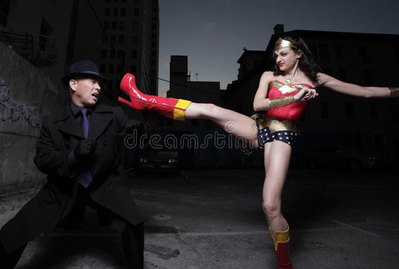 Superheld, der den schlechten Schuft tritt stockfotografie