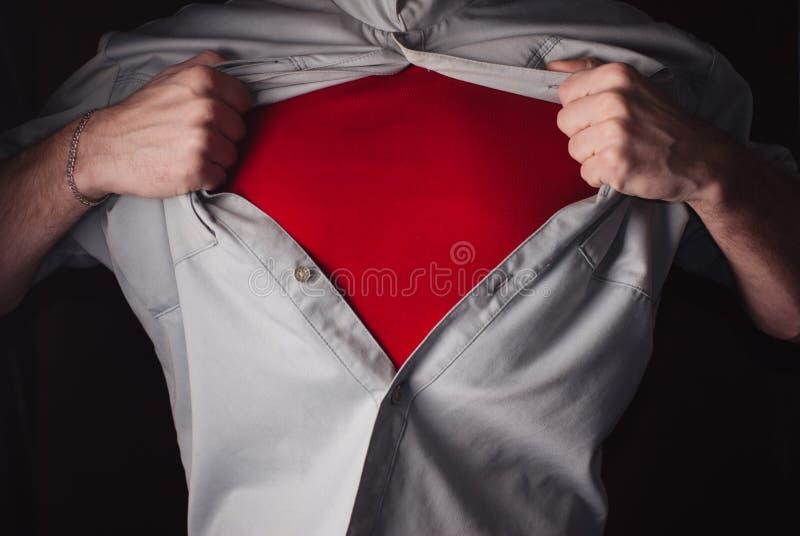 Superheld reißt sein Hemd auf einem dunklen Hintergrund auseinander lizenzfreies stockbild
