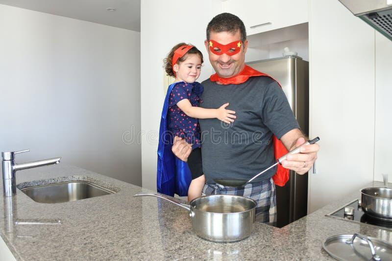 Superheld vader en dochter die samen koken stock afbeeldingen