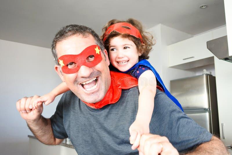 Superheld vader en dochter doen alsof ze samen plezier hebben stock fotografie