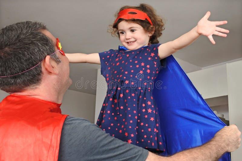 Superheld vader en dochter doen alsof ze samen plezier hebben royalty-vrije stock foto