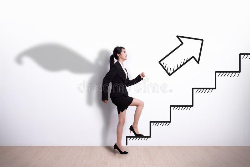 SuperheldGeschäftsfrau mit Treppe stockfotografie