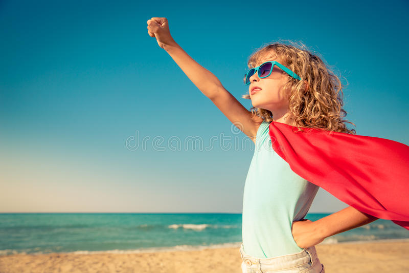 Superheldkind auf dem Strand Reisenkoffer mit Meerblick nach innen lizenzfreies stockbild