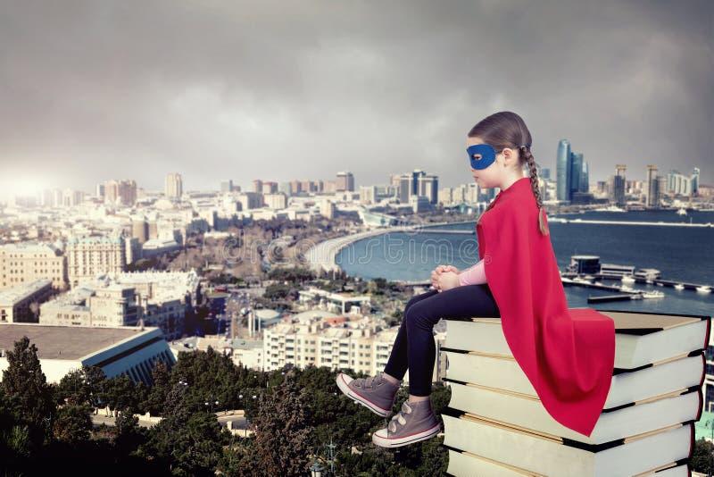 Superheldkind, das auf einem Stapel Büchern gegen städtischen Hintergrund sitzt stockfoto