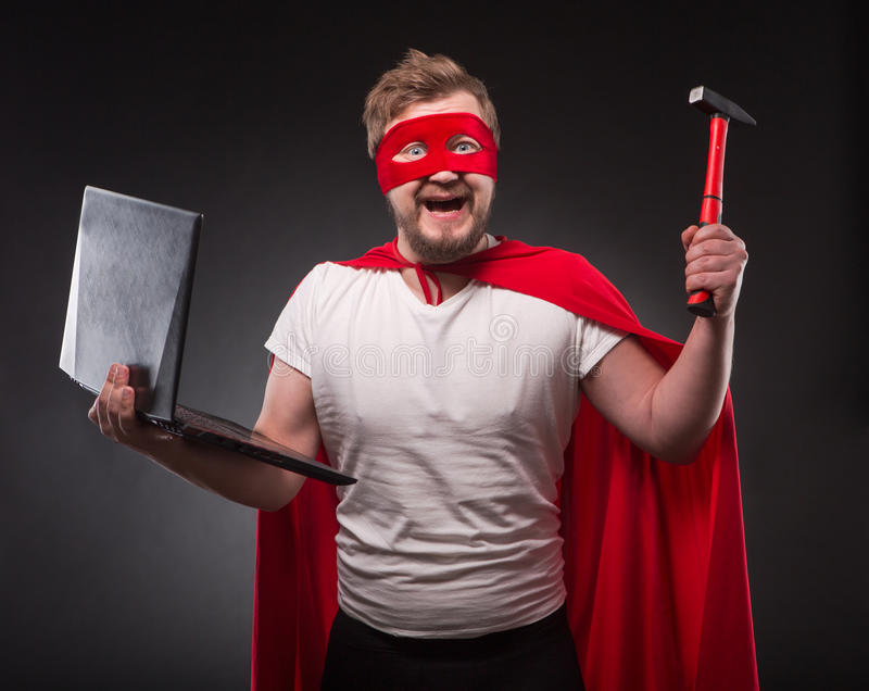 Superheldmann mit Laptop-Computer stockfotografie