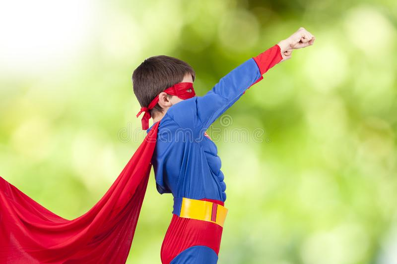 Superhero and the arm up. Child with costume of superhero and the arm up stock image