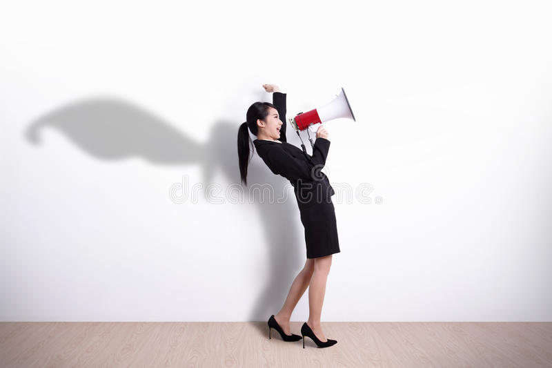 Superhero business woman screaming. Superhero business woman talking in megaphone with white wall background, great for your design or text, asian royalty free stock images