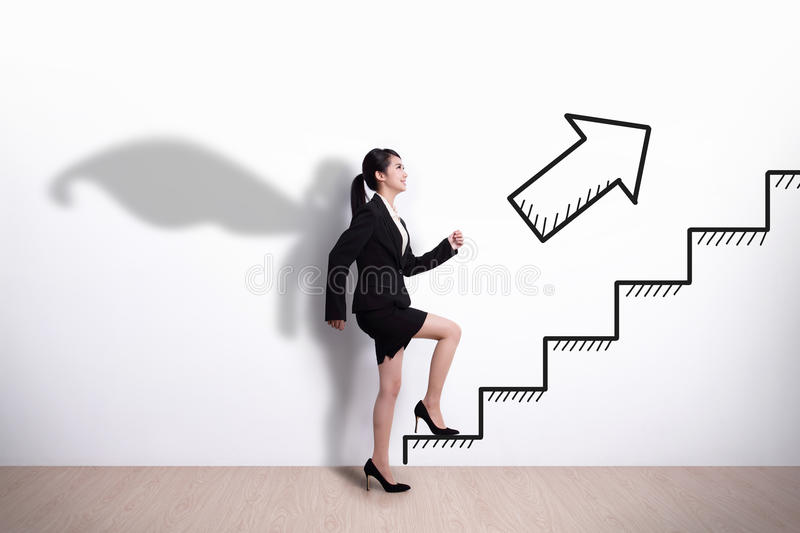 Superhero business woman with stair. Superhero Business woman stepping up on stairs to gain her success with white wall background, asian stock photography