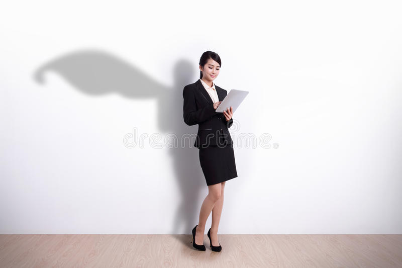 Superhero Business Woman with tablet. Superhero Business Woman using digital tablet pc computer with white wall background, great for your design or text, asian royalty free stock photo