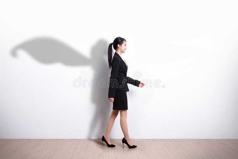Superhero business woman walking. Successful Superhero business woman walking with white wall background, asian royalty free stock image