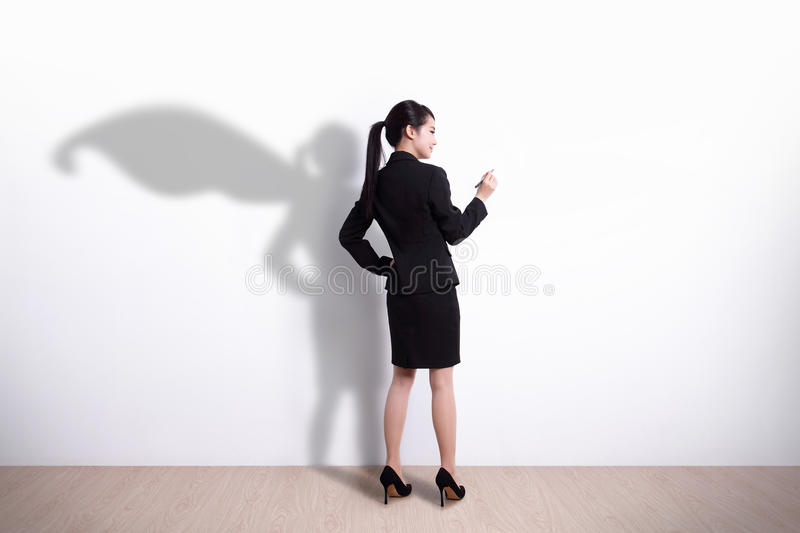 Superhero business woman writing. Back view of Superhero business woman writing something on white wall background, great for your design or text, asian royalty free stock images