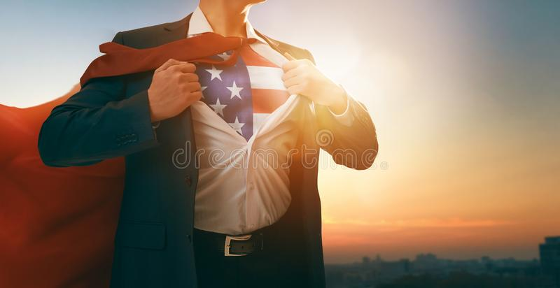 Superhero businessman with American flag on chest stock image