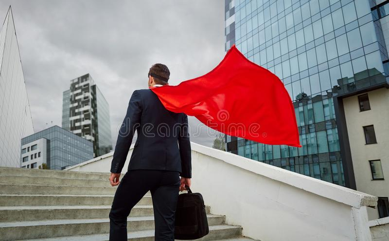 A superhero businessman climbs the stairs to business buildings stock photography