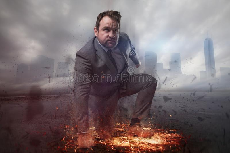 Superhero businessman concept with fire and city background stock photo