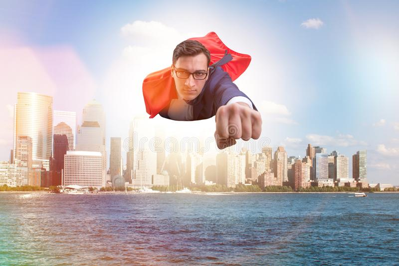 The superhero businessman flying over the city stock photo