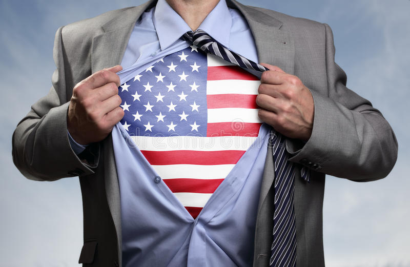 Superhero businessman revealing American flag. Businessman in classic superman pose tearing his shirt open to reveal t shirt with the American flag concept for royalty free stock image