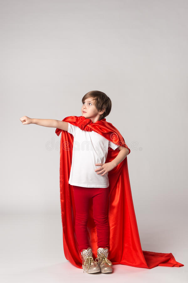 Superhero child pretend what she flying in sky. Kid in red cape stock photo
