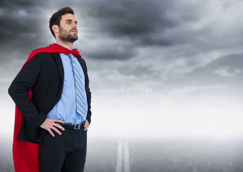 Superhero för affärsman med händer på höfter mot vägen och grå färghimmel med signalljuset royaltyfri illustrationer
