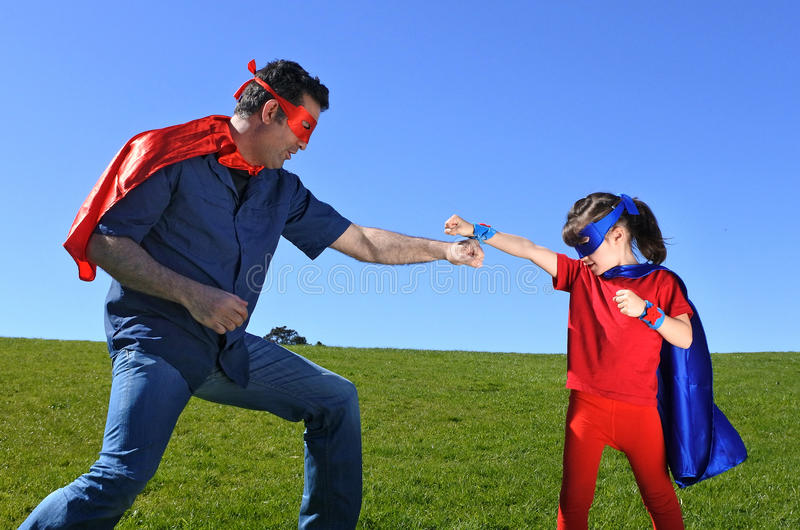 Superhero father shows his daughter how to be a superhero stock image