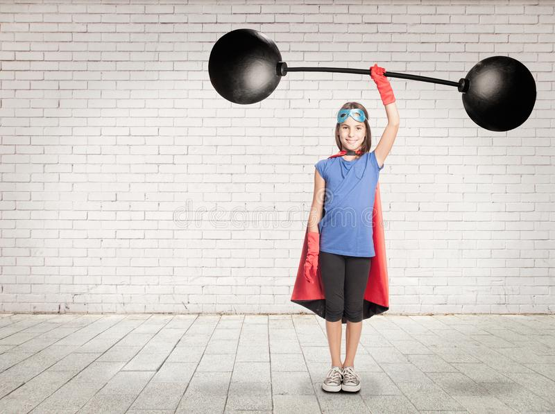 Superhero holding a heavy weight. Little girl superhero holding a heavy weight stock images