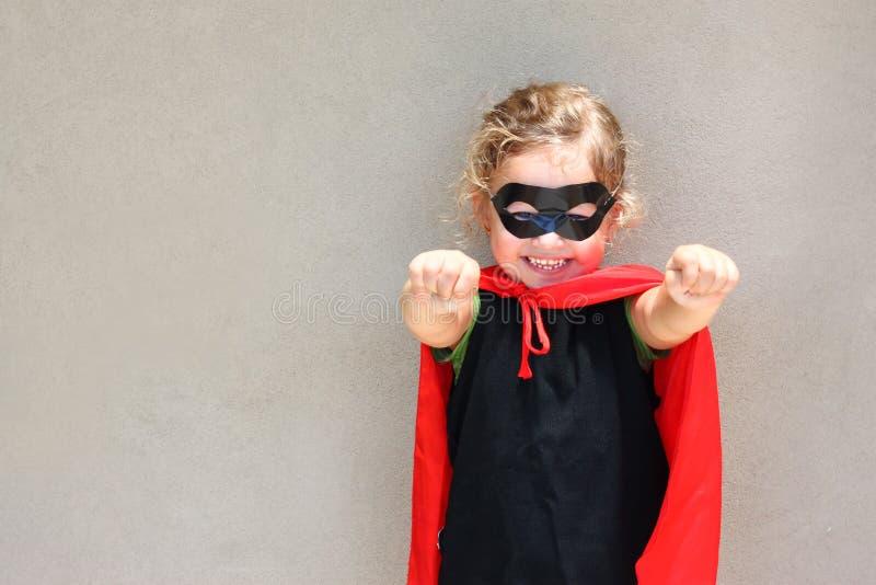 Superhero kid against blue sky background. royalty free stock photography