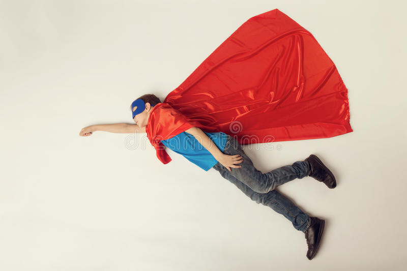 Superhero kid flying. Super hero boy in red cape and blue mask. copyspace, toned.  royalty free stock photography