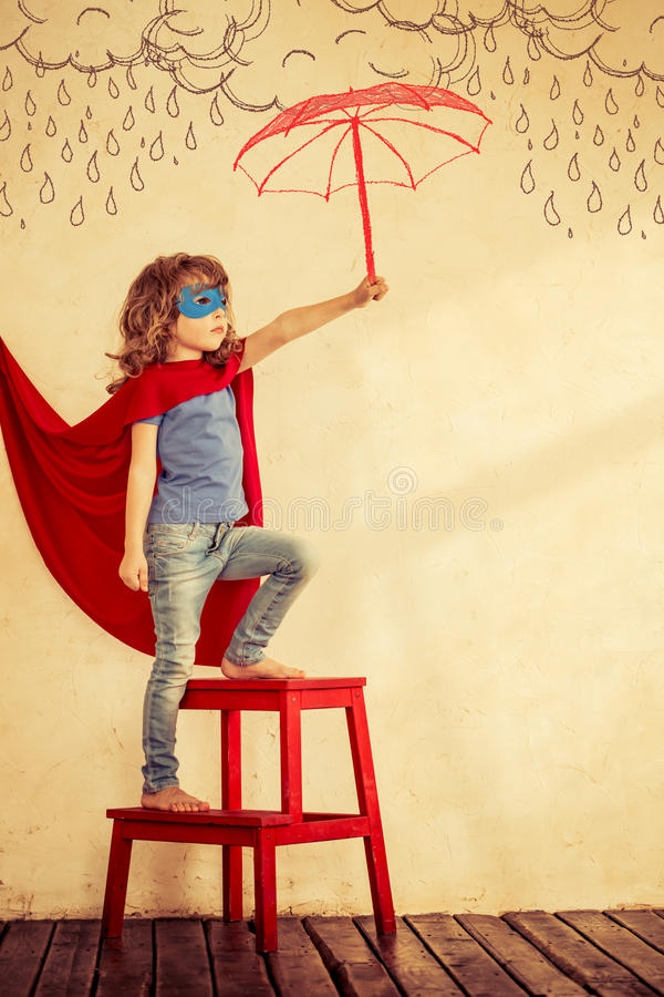 Superhero kid. Full length portrait of superhero kid against grunge wall background royalty free stock photos