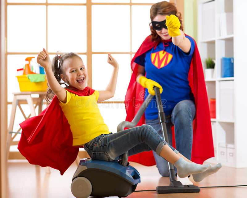 Superhero kid girl and her mother doing laundry together in the living room. Familymiddle-aged woman and child daughter royalty free stock image