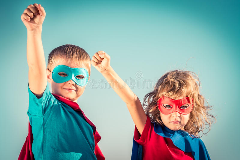 Superhero kids. Superhero children against summer sky background. Kids having fun outdoors. Boy and girl playing. Success and winner concept stock photo