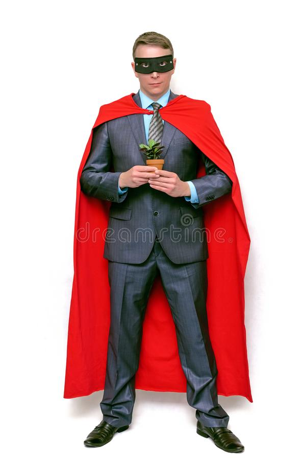 Superhero man holding in hands a green plant tree. royalty free stock photography
