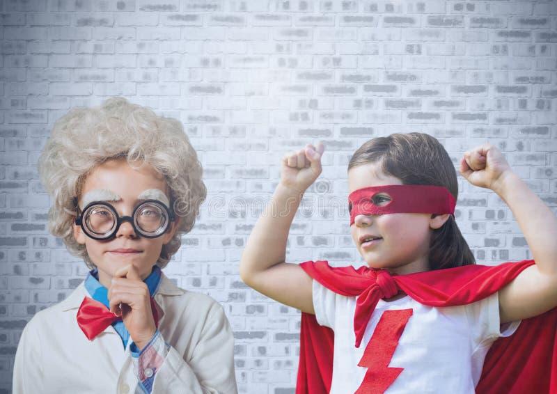 Superhero- och forskareungar framme av tegelstenväggen royaltyfria foton