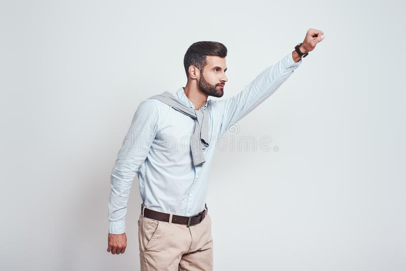 Superhero. Young bearded man is raising his hand up while standing against grey background. Enthusiasm concept. stock photography