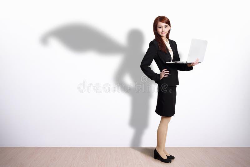 Superheroaffärskvinna med datoren royaltyfria bilder