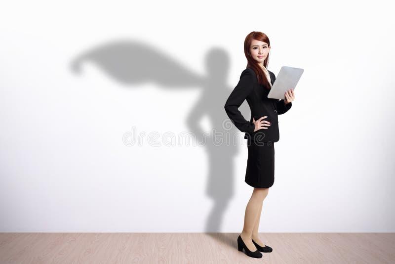 Superheroaffärskvinna med minnestavlan royaltyfri foto