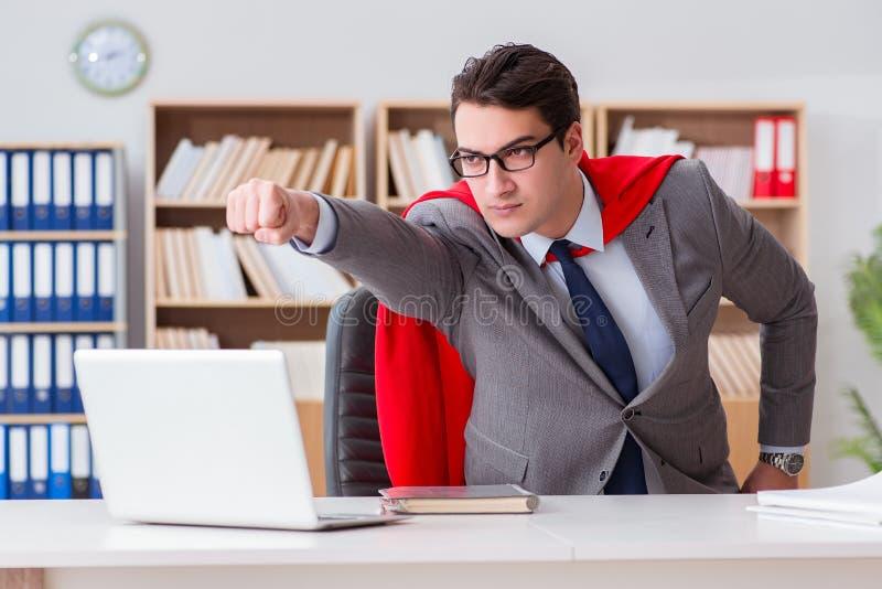 Superheroaffärsmannen som arbetar i kontoret arkivfoton
