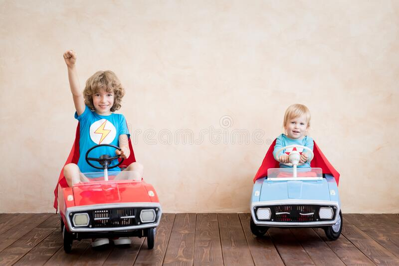 Superheroes children driving toy cars at home royalty free stock photo