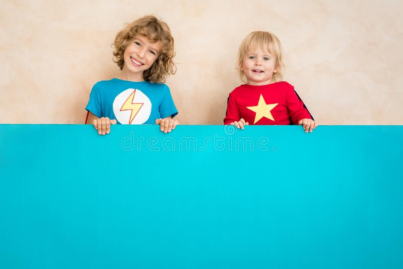 Superheroes children holding blue banner blank royalty free stock photography