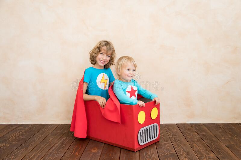 Superheroes children playing in cardboard box stock image