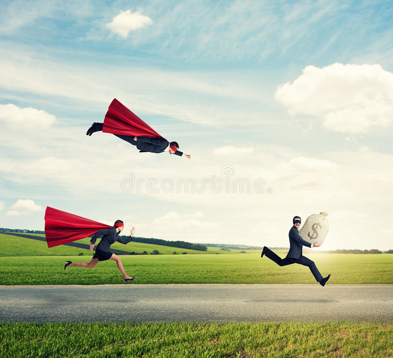 Superheroes trying to catch a thief royalty free stock photo