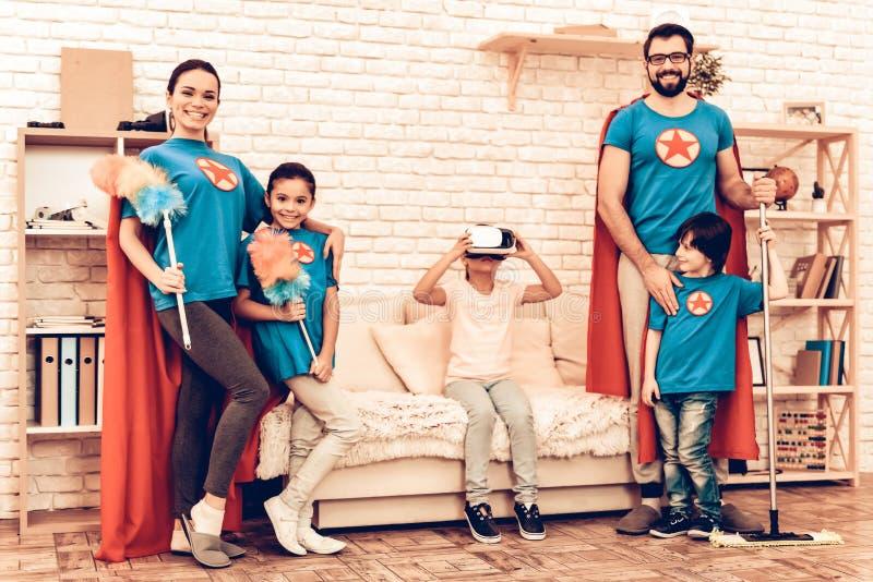 Superheroesfamilj som ser ungen som spelar VR-hörlurar med mikrofon arkivfoto