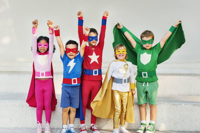 Superheroesungevänner som spelar samhörighetskänslagyckelbegrepp royaltyfria foton
