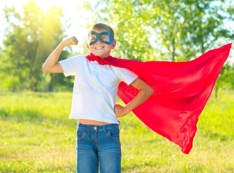Superherojong geitje die zijn spieren tonen stock foto