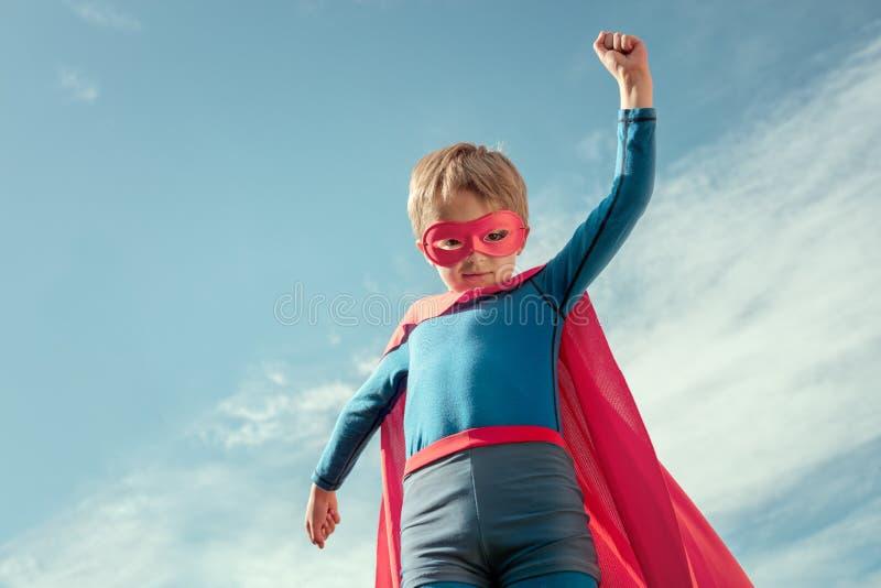 Superherojong geitje in rood kaap en masker stock fotografie