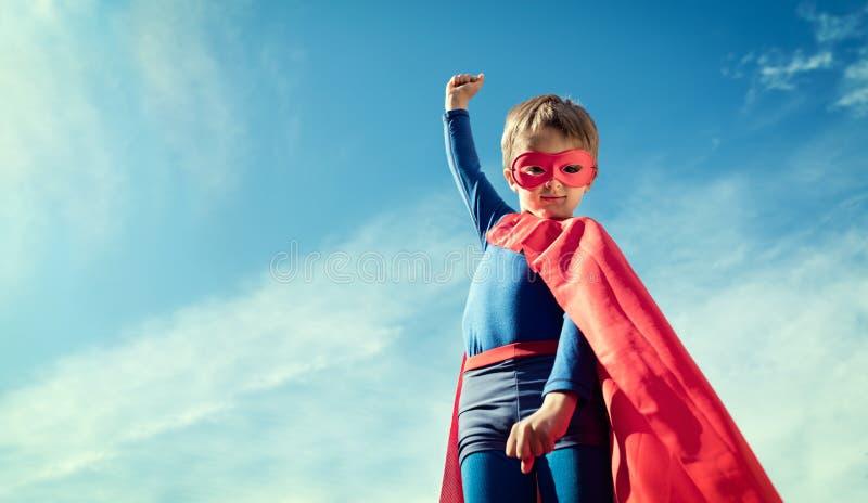 Superherojong geitje in rood kaap en masker stock foto's