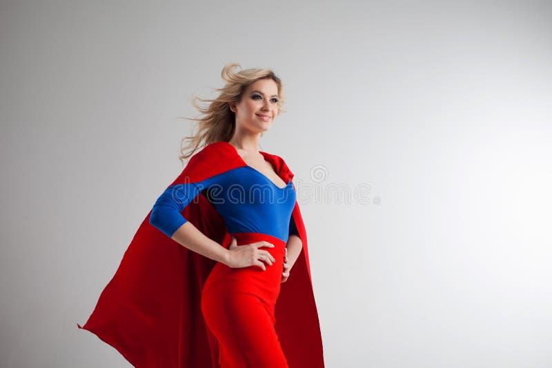 Superherokvinna Ung och härlig blondin i bild av superheroinen i rött växa för udde arkivbild